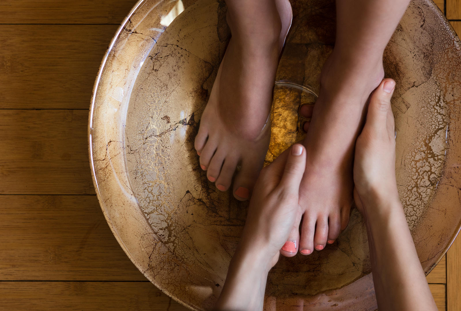 Spa guest receiving a pedicure in a gold bowl