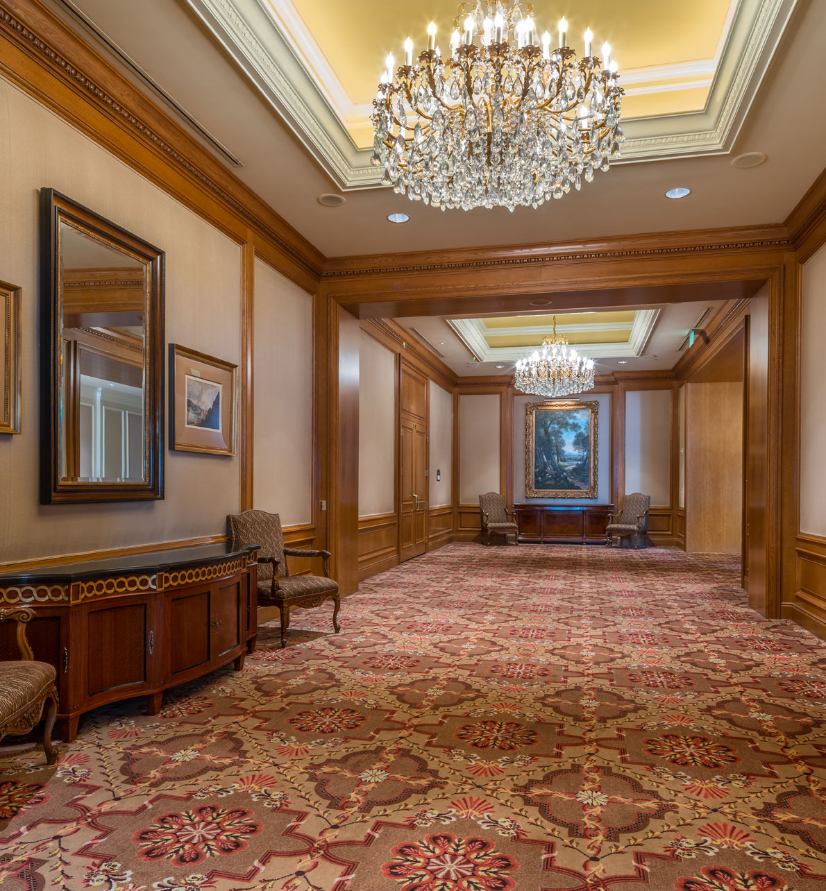 Savoy and Envoy reception area at the Grand America Hotel with chandeliers and wood trim.