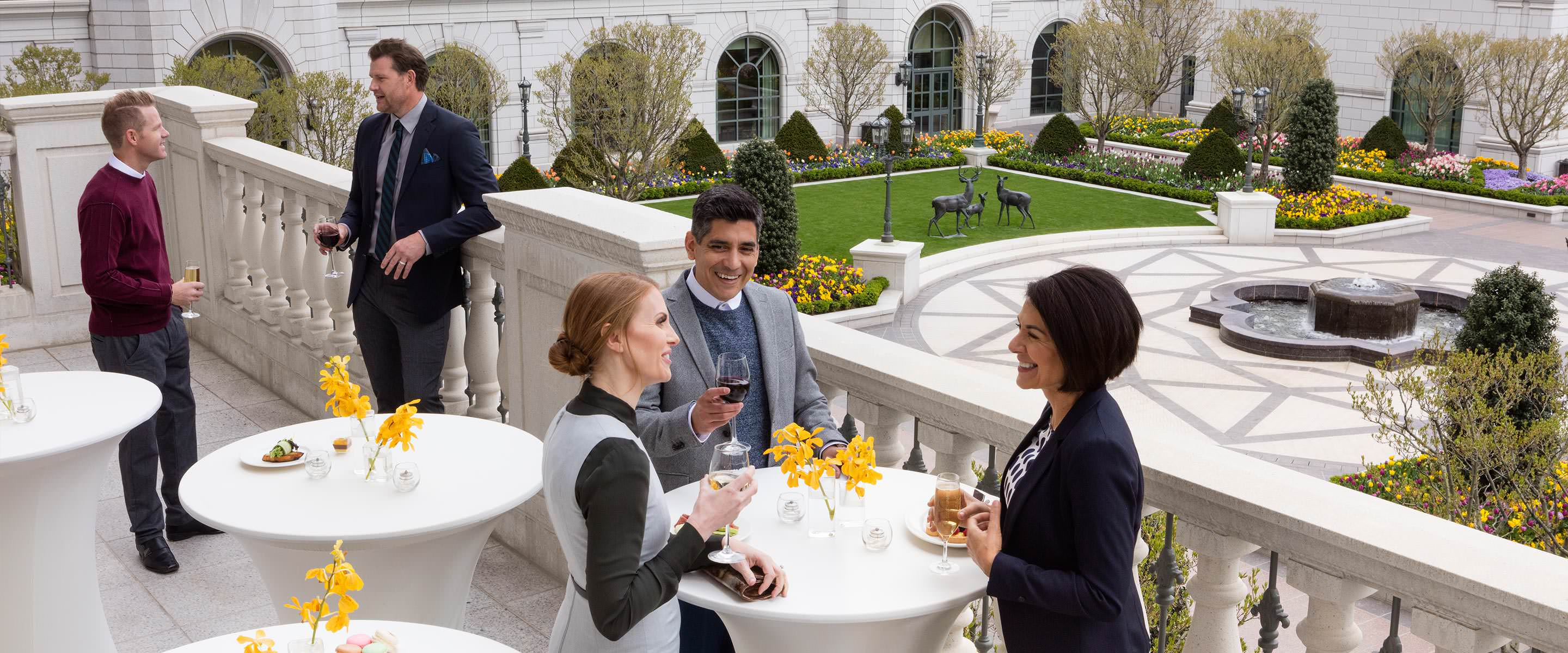 Group of business colleagues at a reception talking and drinking cocktails on the balcony of the third-floor event space at The Grand America Hotel.