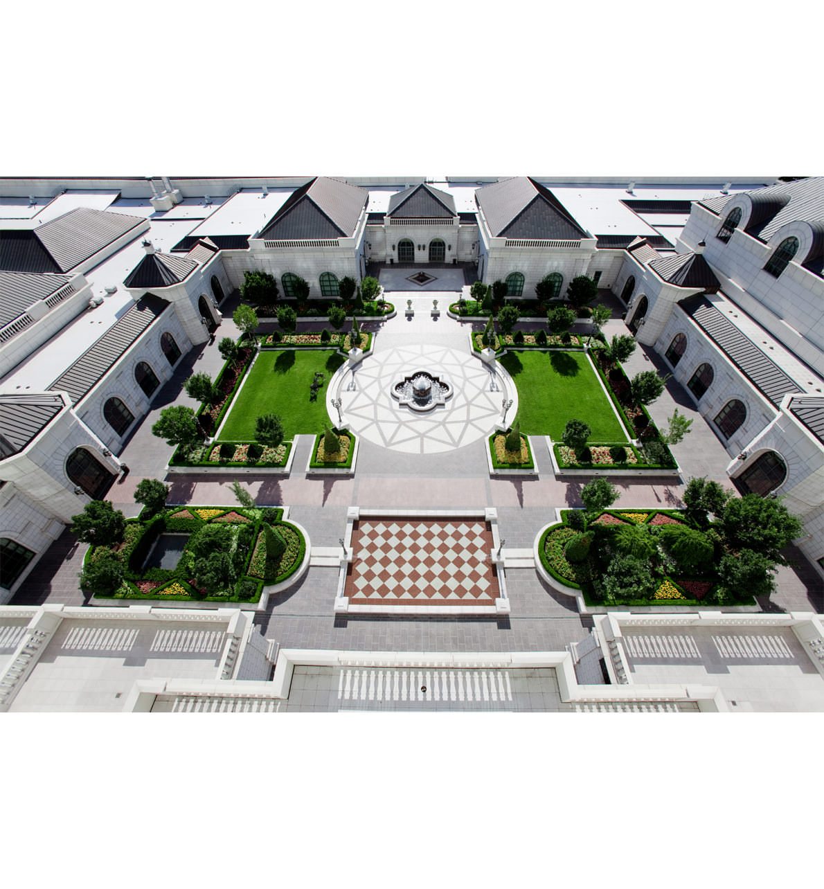 Aerial view of the Garden Courtyard at The Grand America Hotel, featuring green manicured lawns, flower beds and reception space
