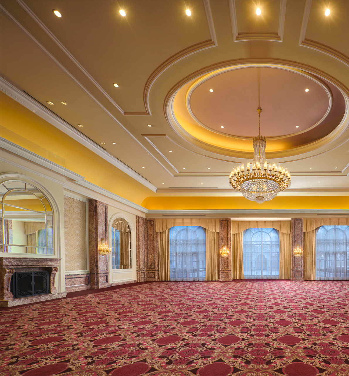 The Grand Salon meeting space with a large center chandelier and fireplace at the Grand America Hotel