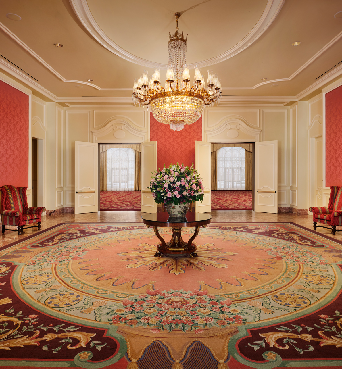 Reception area in the Grand Salon meeting space with hanging chandelier and center table with arrangement of flowers
